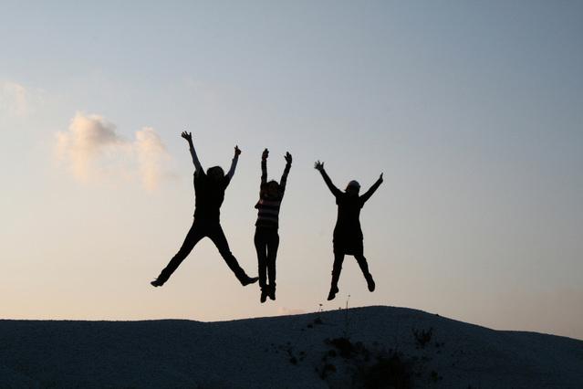 tři skákající postavy v dálce